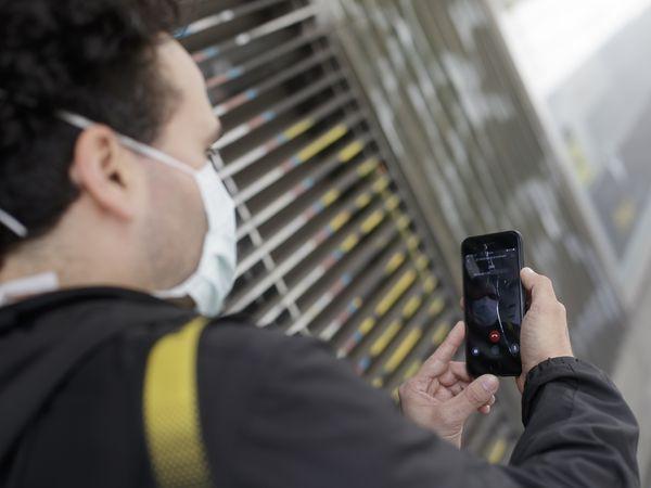 Un hombre protegido con mascarilla realiza una videollamada por su teléfono móvil, una de las formas más habituales de comunicarse durante la pandemia del coronavirus ya que permite tener más